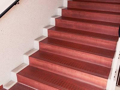 Bodensanierung mit transparenter Lackierung. Ein abgenutzter Treppenboden mit Gumminoppen